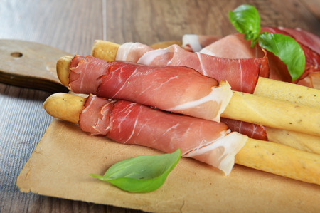 grissini: Grissini bread sticks with ham on old wooden background