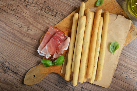 breadstick: Grissini bread sticks with ham on old wooden background