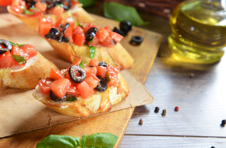 bruschetta with tomatoes, olives and basil photo