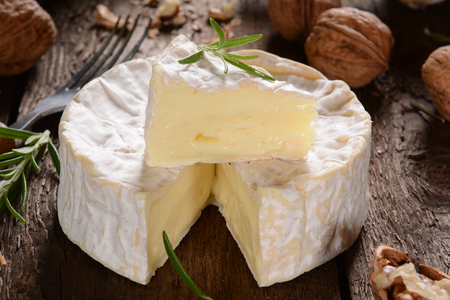camembert: Camembert cheese on a rustic background Stock Photo