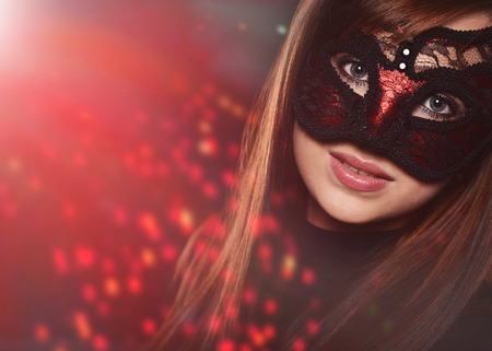 Beautiful caucasian brunette in red carnival mask over black background photo