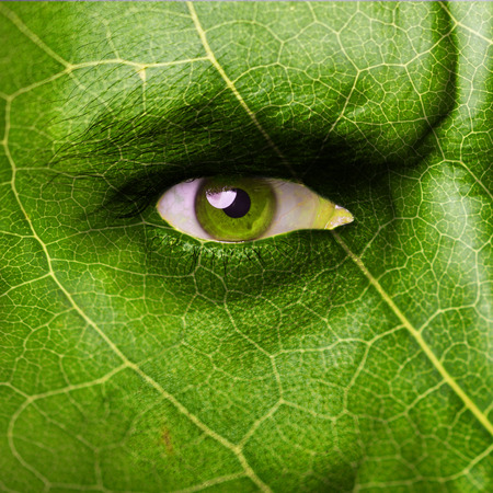 green Leaf texture on human face. Ecology concept.