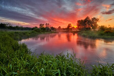 Beautiful summer sunrise over river banks