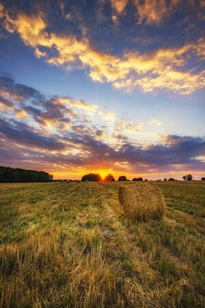 Beautiful summer sunrise over fields with hay bales