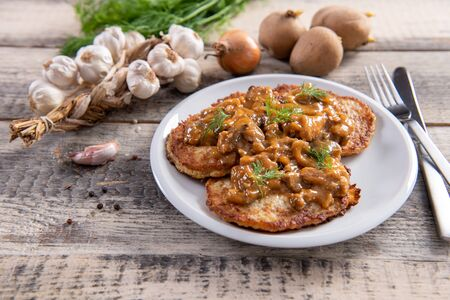 Tasty homemade potato pancakes with meat and mushrooms