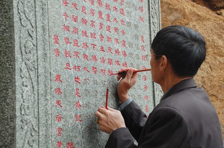 scribe: chinese scribe writing on stone slab