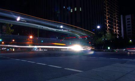 trails of lights: Bus svolta angolo su occupato interesection Archivio Fotografico