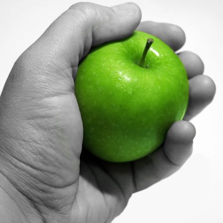 A Green apple being held by a hand photo