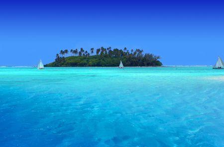 Boats sailing near tropical Motu