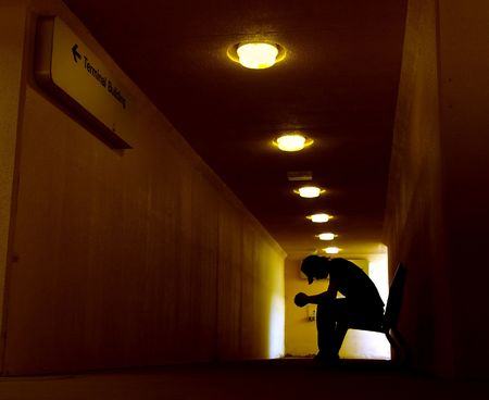 agony: Silhouette of young man in despair Stock Photo