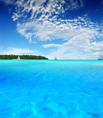 bask: Boats sailing near tropical Island Stock Photo