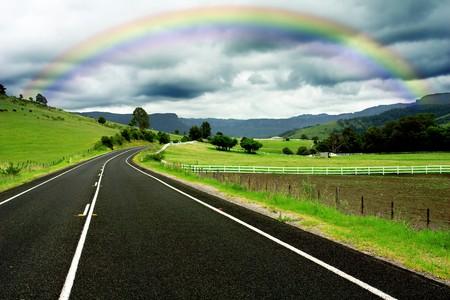 Road winding through farm land and a gorgeous rainbow photo