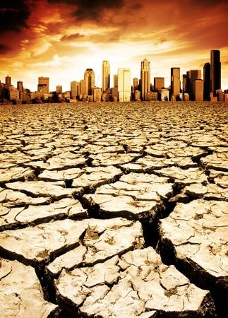 desolate: A city looks over a desolate cracked earth landscape