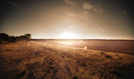 Sun setting over rural farmland photo