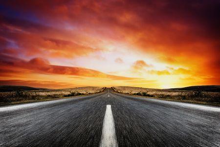 Carretera que conduce a una hermosa puesta de sol Foto de archivo