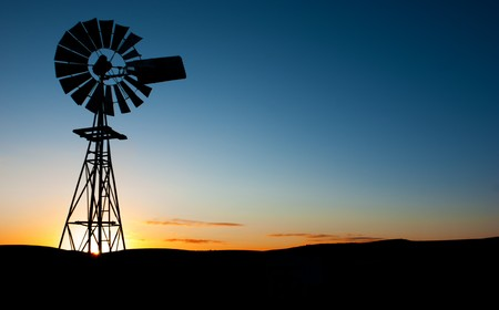 Sun rises behind a windmill Stock Photo