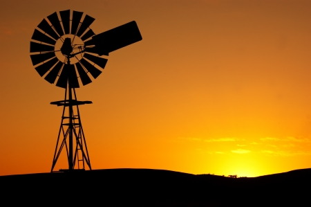 australie landschap: Silhouet van een windmolen op een landelijke boerderij