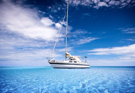 A Yacht travelling through crystal clear tropical waters