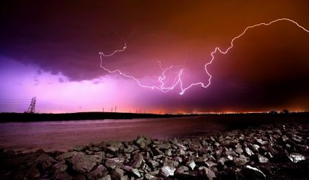 adelaide: LIghtning Strikes over rocks and water Stock Photo