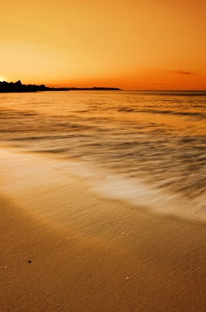 Golden sunset over motion blurred waves splashing on the sand Stock Photo - 9544931