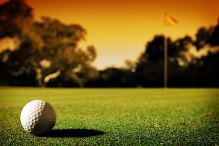 pelota de golf: A largo putt en el hoyo 18 como puesta del sol cierra en