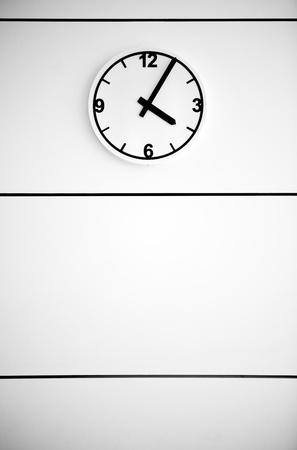 Clock on white wall Standard-Bild