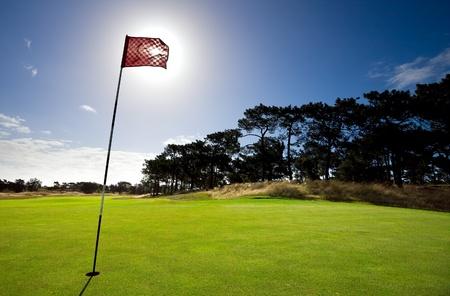 Sun shines behind a golf flag