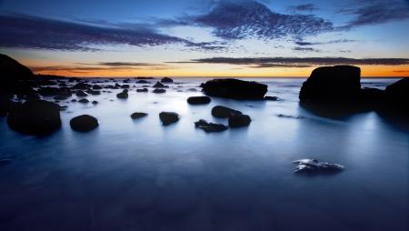 해안 바위와 일몰의 Sihouette