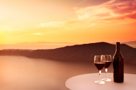 santorini greece: 2 glasses of red wine and  beautiful sunset