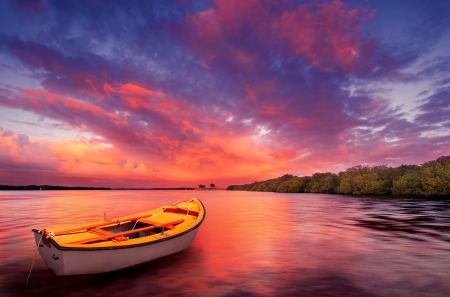 seascape: A rowboat watches an amazing sunset