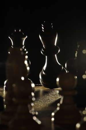 opponents: Falling Chess King sourouned by opponents pawns  lit from the back Stock Photo
