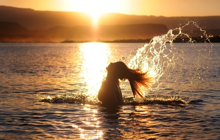 Girl Taking a Bath in Lake Powell at Sunset Stock Photo
