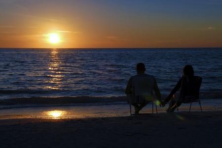 Couple assis sur un transats au coucher du soleil Banque d'images