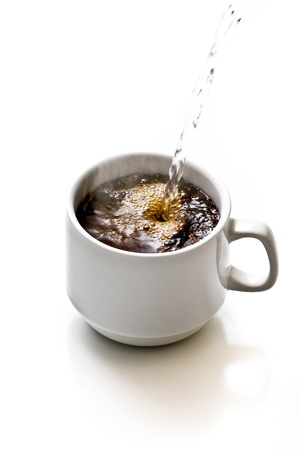 Hot water being poured into cup of coffe photo