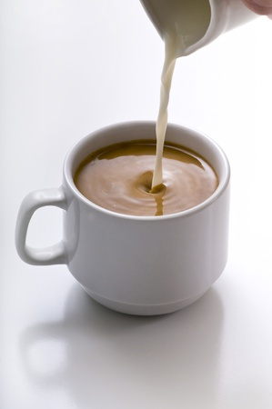 Milk being poured into small cup of coffe.