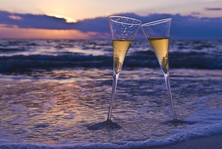 sektglas: Zwei Champagner-Gl�ser am Strand bei Sonnenuntergang Lizenzfreie Bilder