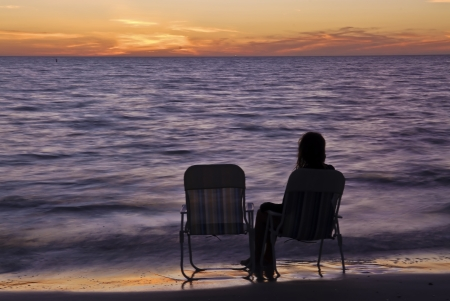 Lonely Girl assis sur une chaise de plage au coucher du soleil