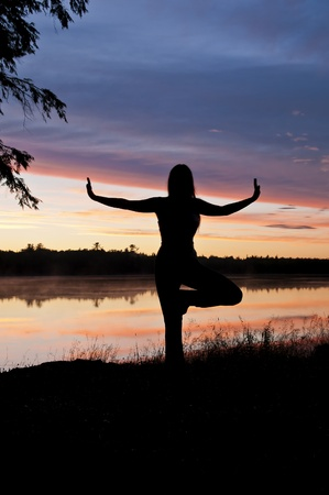 Girl Practicing Yoga by the lake at Sunset photo