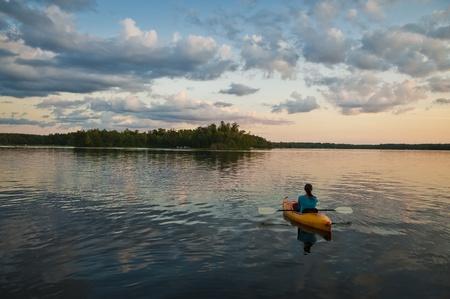 Giirl assis dans le kayak sur le lac au coucher du soleil