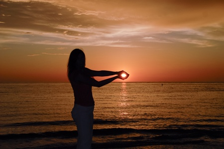 Girl holding the Sun in her hands photo