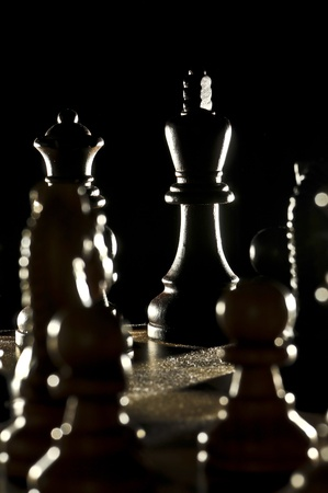 chess board: Chess King sourouned by opponents pawns  lit from the back