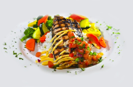 Grilled fish on a white plate with rice and vegetables glass of wine  over white background photo