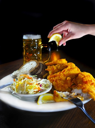 Female Hand squeezing lemon on tasty looking fish fry dish, with tall glass of beer in the background photo