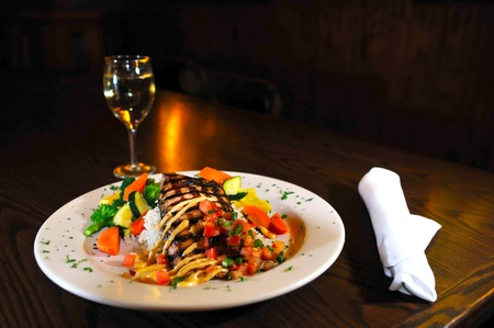 Grilled fish on a white plate with rice and vegetables glass of wine  photo