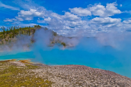 pressurized: Beautifu cerulean geyser against cloudy summer sky
