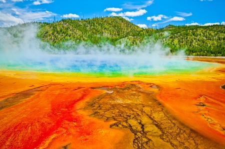 pressurized: Beautiful cerulean geyser surrounded by colorful layers of bacteria, against cloudy blue sky. Stock Photo