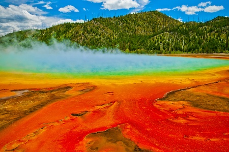 methane: Beautiful cerulean geyser surrounded by colorful layers of bacteria, against cloudy blue sky. Stock Photo