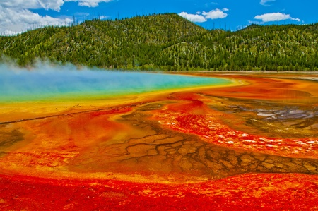 Beautiful cerulean geyser surrounded by colorful layers of bacteria, against cloudy blue sky. Stockfoto