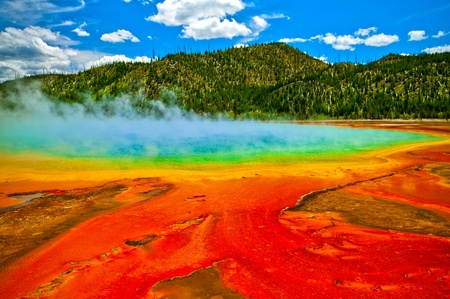 Beautiful cerulean geyser surrounded by colorful layers of bacteria, against cloudy blue sky. Фото со стока