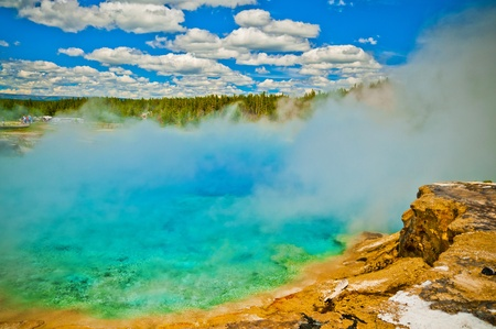 Beautiful cerulean geyser surrounded by colorful layers of bacteria, against cloudy blue sky. Stock Photo - 12827698